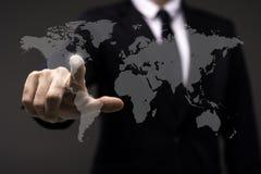 Biznesowy mężczyzna dotyka imaginacyjnego ekran z światową mapą zdjęcie stock