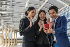 Biznesowy mężczyzna i biznesowa kobieta robi konferenci telefonicznej z someone na telefonie komórkowym Obraz Stock