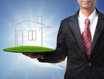 Biznesowy mężczyzna i dom na zieleni lądujemy w ręce Fotografia Stock