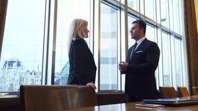 Biznesowy mężczyzna i kobieta stoimy panoramicznym okno w ich biurze fotografia royalty free