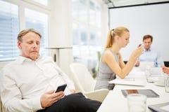 Biznesowy mężczyzna jako konsultant z smartphone zdjęcia royalty free