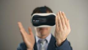 Biznesowy mężczyzna jest ubranym rzeczywistości wirtualnej googles/VR szkła pracować z nowożytnym biurem w zbiory