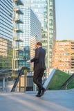 Biznesowy mężczyzna ma wywoławczego telefon - chodzący w nowym finacial centre Mediolan Obraz Royalty Free