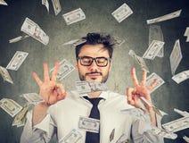 Biznesowy mężczyzna medytuje pod pieniądze deszczem zdjęcia royalty free