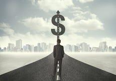 Biznesowy mężczyzna na drogowym kłoszeniu w kierunku dolarowego znaka Zdjęcie Royalty Free