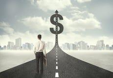Biznesowy mężczyzna na drogowym kłoszeniu w kierunku dolarowego znaka Fotografia Royalty Free