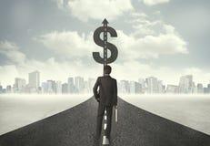 Biznesowy mężczyzna na drogowym kłoszeniu w kierunku dolarowego znaka Zdjęcie Stock