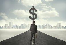 Biznesowy mężczyzna na drogowym kłoszeniu w kierunku dolarowego znaka Fotografia Stock