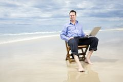 Biznesowy mężczyzna na plaży z laptopem obrazy stock