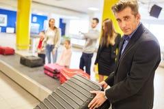 Biznesowy mężczyzna na podróży służbowej na bagażu pasku fotografia stock