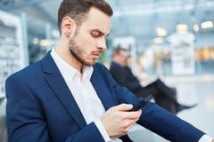 Biznesowy mężczyzna na podróży służbowej czyta wiadomość tekstową obrazy stock