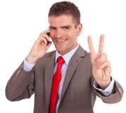 Biznesowy mężczyzna na telefonu zwycięstwa znaku Fotografia Stock