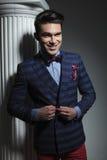 Biznesowy mężczyzna ono uśmiecha się podczas gdy zamykający jego kurtkę Fotografia Stock