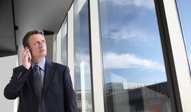 Biznesowy mężczyzna opowiada na spojrzeniach i telefonie przez okno w biurze Obraz Stock