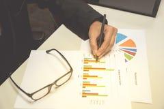 Biznesowy mężczyzna patrzeje i pisze przy biznesowych map, wykresów i dokumentów tłem, dla analizować biznes Zdjęcia Stock