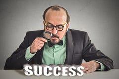 Biznesowy mężczyzna patrzeje przez powiększać przy sukcesu znakiem - szkło Obrazy Royalty Free