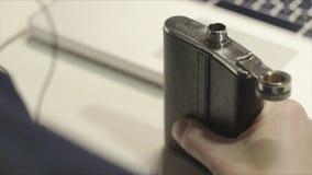 Biznesowy mężczyzna pije alkohol od kolby w biurze zdjęcie wideo