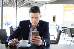 Biznesowy mężczyzna pije filiżankę kawy podczas gdy siedzący z jego telefonem w kawiarni Zdjęcia Royalty Free
