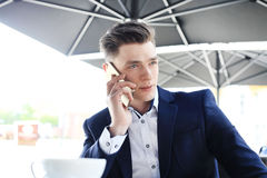 Biznesowy mężczyzna pije filiżankę kawy podczas gdy siedzący z jego telefonem w kawiarni Fotografia Stock