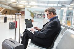 Biznesowy mężczyzna pisać na maszynie na jego laptopie w lotnisku zdjęcie stock