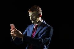 Biznesowy mężczyzna pod maskowym przebraniem jest Anonimowy i insynuować ten jest anarchistą lub hackerem zdjęcie stock
