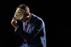 Biznesowy mężczyzna pod maskowym przebraniem jest Anonimowy i insynuować ten jest anarchistą lub hackerem obraz stock