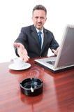 Biznesowy mężczyzna pokazuje papieros na ashtray przy biurem Fotografia Stock