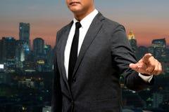 Biznesowy mężczyzna pokazuje rękę i palec z miastem zaświeca w backgrou Fotografia Royalty Free