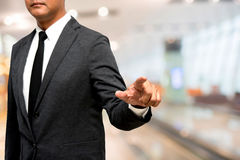 Biznesowy mężczyzna pokazuje rękę i palec z plamy sala sposobu backgrou Zdjęcia Stock