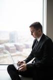 biznesowy mężczyzna pracuje blisko panoramicznego miasta okno na laptopie Zdjęcie Royalty Free