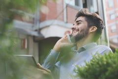 Biznesowy mężczyzna pracuje na cyfrowej pastylce w ulicznej kawiarni zdjęcia royalty free