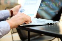 Biznesowy mężczyzna pracuje pieniężne postacie na outside i analizuje wykresy na laptopie Zdjęcie Royalty Free