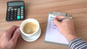 Biznesowy mężczyzna przy biurkiem ustawia kleszczową ocenę na ilości liście kontrolnej zdjęcie wideo