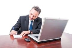 Biznesowy mężczyzna przy biurowym writing w notepad Zdjęcie Royalty Free