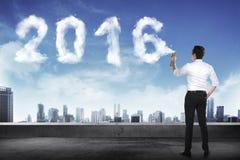Biznesowy mężczyzna rozpyla biel 2016 rok chmury kształt Fotografia Royalty Free