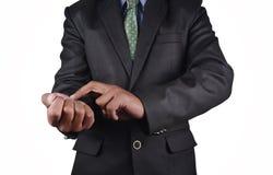 Biznesowy mężczyzna sprawdza żyłę w czarnym kostiumu odizolowywającym zdjęcie royalty free