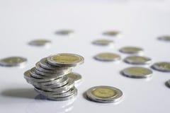 Biznesowy mężczyzna stawia monetę na monetach broguje oszczędzanie banka i uzasadnia jego pieniądze wszystko w finansowym księgow zdjęcie stock