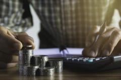 Biznesowy mężczyzna stawia monetę na monetach broguje oszczędzanie banka i uzasadnia jego pieniądze wszystko w finansowym księgow zdjęcia stock