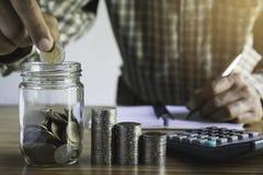 Biznesowy mężczyzna stawia pieniądze w szklanym słoju ratować, pieniężny, księgowości pojęcie zdjęcia stock