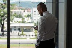 Biznesowy mężczyzna Texting Na telefonie komórkowym W Nowożytnym biurze Obrazy Stock