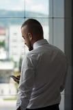 Biznesowy mężczyzna Texting Na telefonie komórkowym W Nowożytnym biurze Zdjęcia Royalty Free