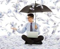 Biznesowy mężczyzna trzyma chwytającego pieniądze i parasol zdjęcie stock