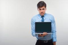 Biznesowy mężczyzna trzyma laptop przeciw białemu tłu Fotografia Royalty Free