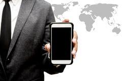 Biznesowy mężczyzna trzyma mądrze telefon z światowej mapy grafiką Fotografia Royalty Free