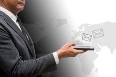 Biznesowy mężczyzna trzyma mądrze telefon z listową grafiką m i światem Fotografia Stock