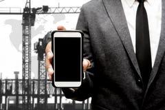 Biznesowy mężczyzna trzyma mądrze telefon z plama wizerunkiem budowa Zdjęcia Stock
