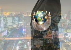 Biznesowy mężczyzna trzyma małego świat w jego rękach z pejzażem miejskim Zdjęcia Stock