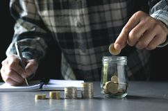 Biznesowy mężczyzna trzyma monetę stawiać dalej wierzchołek stos monety obrazy royalty free