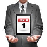 Biznesowy mężczyzna trzyma pastylkę pokazuje 1 Jan nowego roku dzień ic Fotografia Stock