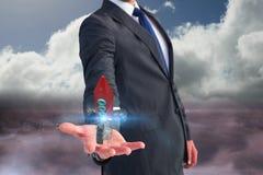 Biznesowy mężczyzna trzyma rakietę na jego ręce przeciw nieba tłu Obraz Royalty Free